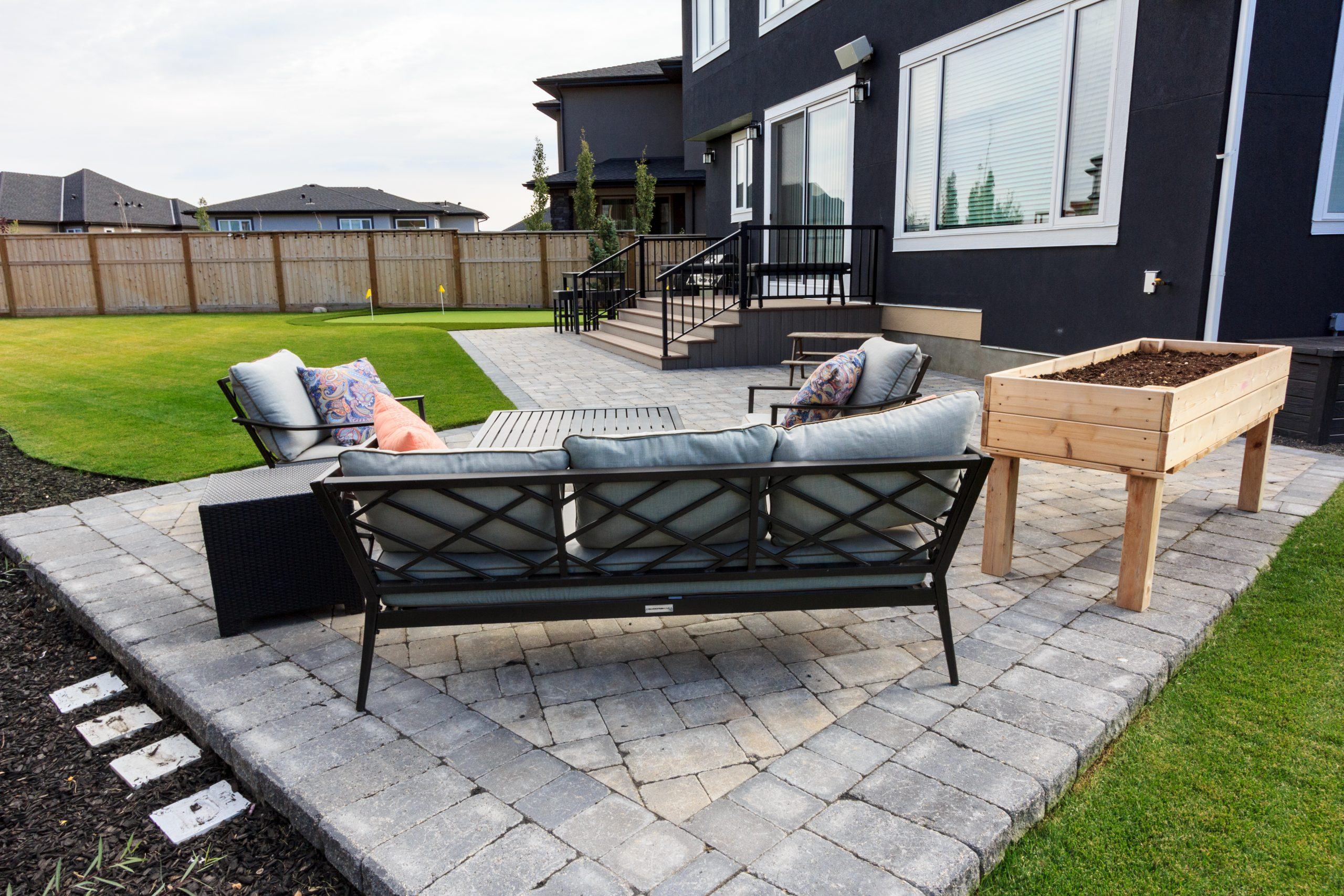 Backyard landscaping with large patio and synthetic putting green